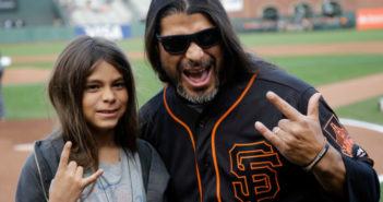 Metallica's Robert Trujillo, right, poses for pictures with his son Tye before a baseball game between the San Francisco Giants and Colorado Rockies Friday, May 6, 2016, in San Francisco. (AP Photo/Marcio Jose Sanchez)