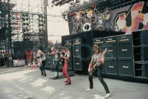 Judas Priest performs during the US Festivals. On stage (from left) are: K.K. Downing, Rob Halford, Glenn Tipton, and Ian Hill. On a platform above them is drummer Dave Holland. The multi-day music festival is presented by Steve Wozniak, co-founder of Apple Computers. May 1983 San Bernardino, California, USA